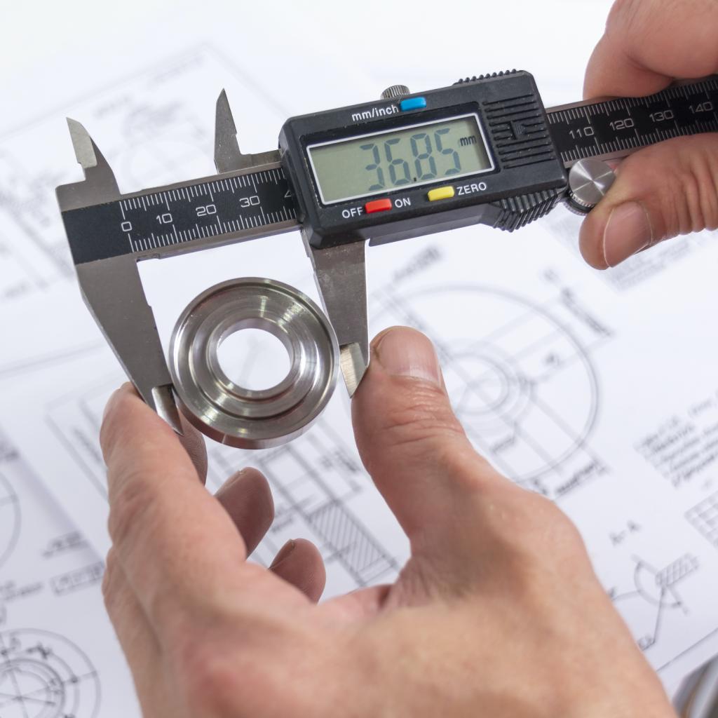 Hands of an engineer measures a metal part